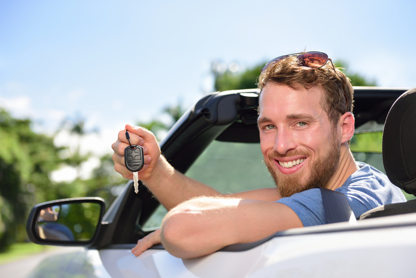 Man driving rental car showing new car keys happy. Young adult excited on road trip with key for cars leasing or rental or purchase.